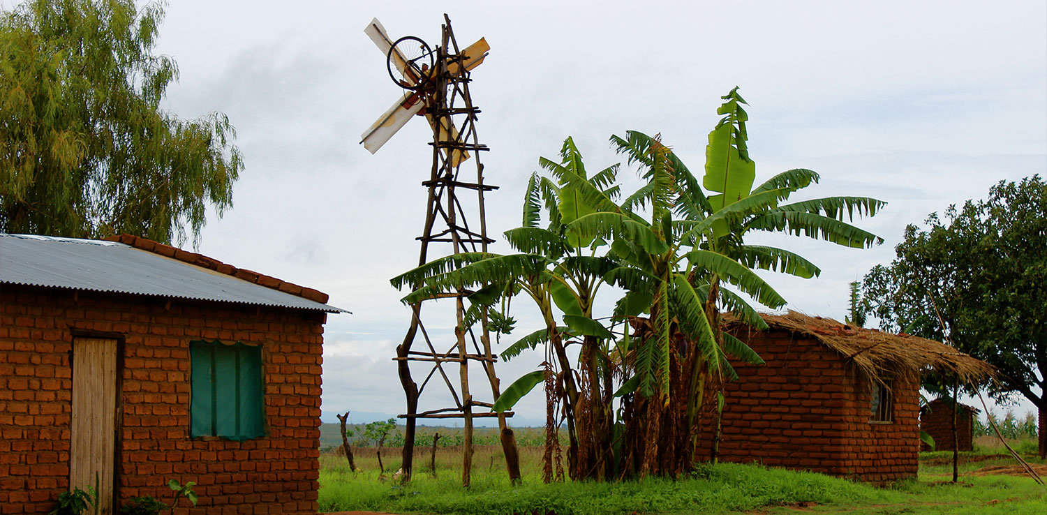 A windmill made of wood between two houses with banana trees