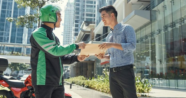 A Grab's driver delivering a document to a customer