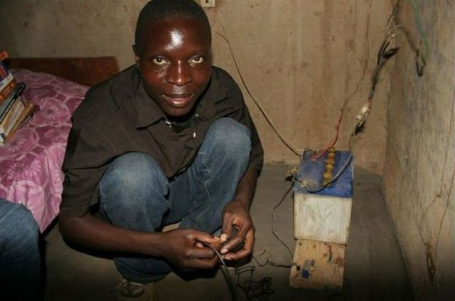 William Kamkwamba squatting in front of a hand-crafted machine
