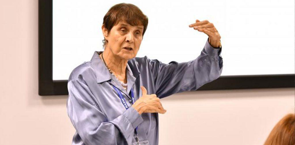 lena dominelli wears a purple shirt, giving a lecture