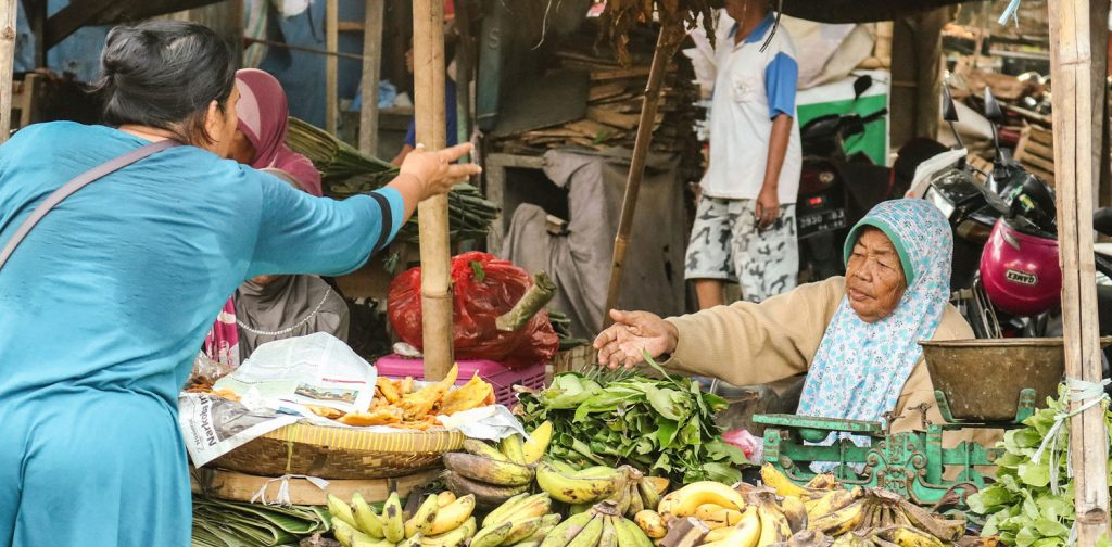 A woman in blue shirt is buying local bananas from a vendor at traditional market.